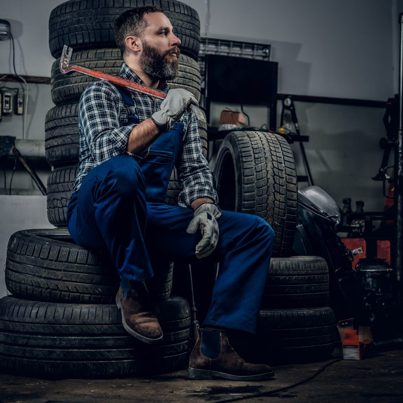 Bearded mechanic sits on an old car's tire in a garage.