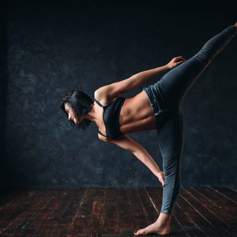 Body flexibility, contemp style dancing in dance class. Female dancer poses in studio