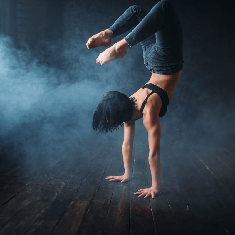 Body flexibility, contemp style dancer in dance class. Female performer poses in gymnastic studio